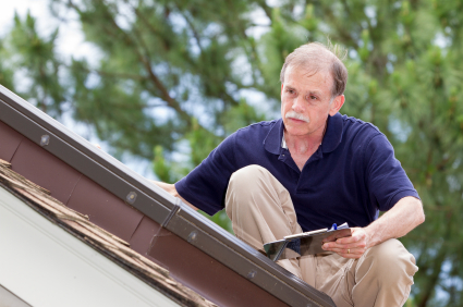 An inspector on the roof examines a skylight